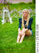 Купить «Young blond woman sits on grassy lawn in park, dog sits behind her out of focus», фото № 25836508, снято 23 июля 2015 г. (c) Losevsky Pavel / Фотобанк Лори