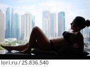 Купить «Woman in underwear is on windowsill with view of skyscrapers in city», фото № 25836540, снято 7 ноября 2015 г. (c) Losevsky Pavel / Фотобанк Лори