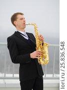 Купить «Man in suit plays saxophone on roof of tall building at winter day», фото № 25836548, снято 13 февраля 2016 г. (c) Losevsky Pavel / Фотобанк Лори