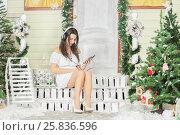 Купить «Full portrait of young woman sitting on threshold of fake home and listening music in headphones. Christmas interior studio», фото № 25836596, снято 14 декабря 2014 г. (c) Losevsky Pavel / Фотобанк Лори
