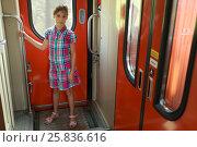 Купить «Young girl standing in vestibule of train and hold handrail», фото № 25836616, снято 5 августа 2014 г. (c) Losevsky Pavel / Фотобанк Лори