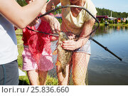 Купить «Mother removes a hook from a mouth of the caught carp at pond bank, two children stand near», фото № 25836660, снято 25 июля 2015 г. (c) Losevsky Pavel / Фотобанк Лори