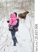 Купить «Young man with baby in arms takes snapshot of elk feeds in winter park», фото № 25837008, снято 25 января 2015 г. (c) Losevsky Pavel / Фотобанк Лори