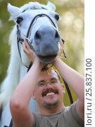 Купить «Handsome smiling man in glasses under white horse head in park», фото № 25837100, снято 24 сентября 2015 г. (c) Losevsky Pavel / Фотобанк Лори
