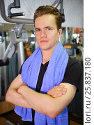 Купить «Happpy handsome man with towel stands after training in fitness club», фото № 25837180, снято 20 июня 2015 г. (c) Losevsky Pavel / Фотобанк Лори