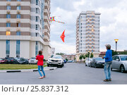 Купить «Brother and sister playing with flying snakes in yard of multistory building on summer evening, focus on buildings», фото № 25837312, снято 20 июня 2014 г. (c) Losevsky Pavel / Фотобанк Лори