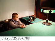 Купить «SAMARA, RUSSIA - MAY 8, 2015: Little boy (with model release) sits at table with green cloth and lamp in Stalins bunker», фото № 25837708, снято 8 мая 2015 г. (c) Losevsky Pavel / Фотобанк Лори