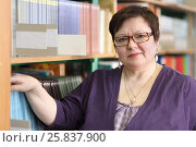 Купить «MOSCOW - MAR 20, 2015: Teacher in blue jacket and spectacles on background of shelves with books. Secondary school number 430 in Moscow operates since 1981», фото № 25837900, снято 20 марта 2015 г. (c) Losevsky Pavel / Фотобанк Лори