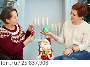 Купить «Two women sit on floor with christmas balls near fireplace with candles», фото № 25837908, снято 24 декабря 2014 г. (c) Losevsky Pavel / Фотобанк Лори