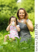 Купить «Little girl in wreath drink milk and her mother smiles in sunny park», фото № 25837956, снято 24 июня 2015 г. (c) Losevsky Pavel / Фотобанк Лори
