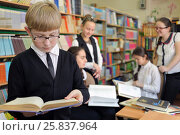 Купить «Student in black jacket and glasses on background of shelves with books and other students, read book, shallow dof», фото № 25837964, снято 20 марта 2015 г. (c) Losevsky Pavel / Фотобанк Лори