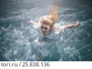Купить «Young blond woman in white dress swims with her eyes close in swimming pool underwater», фото № 25838136, снято 14 мая 2016 г. (c) Losevsky Pavel / Фотобанк Лори