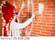 Купить «Young woman dressed in costume made of red and white feathers paints on the brick wall with spray», фото № 25838208, снято 13 февраля 2015 г. (c) Losevsky Pavel / Фотобанк Лори