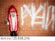 Купить «Young woman dressed in costume made of red and white feathers stands her back to the brick wall and holding spray can», фото № 25838216, снято 13 февраля 2015 г. (c) Losevsky Pavel / Фотобанк Лори