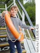 Купить «Smiling boy in striped vest with lifebouy ring over shoulder stands on pleasure boat deck», фото № 25838428, снято 23 мая 2015 г. (c) Losevsky Pavel / Фотобанк Лори