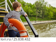 Купить «Boy in striped vest with lifebouy ring under his arm stands on pleasure boat deck looking at water.», фото № 25838432, снято 23 мая 2015 г. (c) Losevsky Pavel / Фотобанк Лори