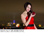Купить «Half-length portrait of young woman in red dress stands at roof railing holding red apple in hand», фото № 25838572, снято 13 февраля 2015 г. (c) Losevsky Pavel / Фотобанк Лори