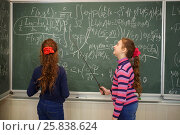 Купить «Two girls stand near blackboard with formulas in classroom and hold pointers», фото № 25838624, снято 7 апреля 2016 г. (c) Losevsky Pavel / Фотобанк Лори