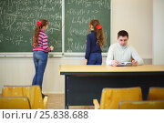 Купить «Two girls with pointers stand near blackboard with formulas and teacher looks into book in classroom, focus on man», фото № 25838688, снято 7 апреля 2016 г. (c) Losevsky Pavel / Фотобанк Лори