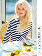Купить «Blonde pretty woman in striped t-shirt sits at table with courses in restaurant», фото № 25838816, снято 25 августа 2015 г. (c) Losevsky Pavel / Фотобанк Лори