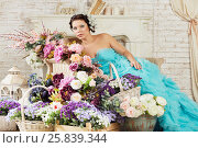 Купить «Woman in blue fluffy dress reclines on couch in room with mass of flowers», фото № 25839344, снято 29 марта 2015 г. (c) Losevsky Pavel / Фотобанк Лори