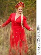 Купить «Pretty woman in red dress and traditional russian kokoshnik with long braid outdoor», фото № 25839384, снято 15 октября 2015 г. (c) Losevsky Pavel / Фотобанк Лори