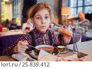 Купить «Girl eats first course sitting at table in cafe», фото № 25839412, снято 28 декабря 2014 г. (c) Losevsky Pavel / Фотобанк Лори
