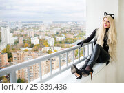 Beautiful sexy woman in latex cats costume is sitting on balcony in city. Стоковое фото, фотограф Losevsky Pavel / Фотобанк Лори