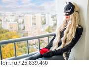 Pretty woman with black cats ears holds red heart and sits on balcony in city. Стоковое фото, фотограф Losevsky Pavel / Фотобанк Лори