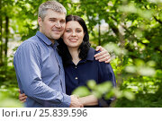 Купить «Half-length portrait of grey-haired man and dark-haired wooman standing embraced in summer park», фото № 25839596, снято 22 мая 2016 г. (c) Losevsky Pavel / Фотобанк Лори