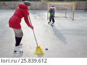 Купить «Woman with broom scores puck into the goal with a boy», фото № 25839612, снято 21 февраля 2015 г. (c) Losevsky Pavel / Фотобанк Лори