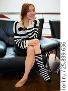 Купить «Happy girl with braces in a black and white striped sweater is sitting cross-legged in one knee sock», фото № 25839636, снято 21 февраля 2015 г. (c) Losevsky Pavel / Фотобанк Лори
