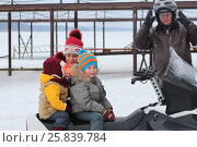 Купить «The mother prepares two children to ride with his father on a snowmobile, focus on boy», фото № 25839784, снято 22 февраля 2015 г. (c) Losevsky Pavel / Фотобанк Лори