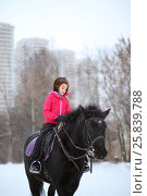 Купить «Portrait of young girl on a black horse at the winter equestrian site in front of trees and buildings», фото № 25839788, снято 5 января 2015 г. (c) Losevsky Pavel / Фотобанк Лори
