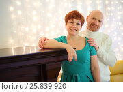 Купить «Happy woman in a green dress and a man near the fireplace, focus on woman», фото № 25839920, снято 22 февраля 2015 г. (c) Losevsky Pavel / Фотобанк Лори