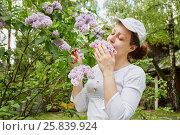 Купить «Young woman inhales the fragrance of lilacs», фото № 25839924, снято 30 мая 2015 г. (c) Losevsky Pavel / Фотобанк Лори