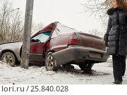 Купить «Woman dressed in winter coat stands near damaged car crashed into lamppost», фото № 25840028, снято 9 января 2015 г. (c) Losevsky Pavel / Фотобанк Лори