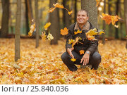 Купить «Young man in black jacket in autumn park, crouched near tree, throws up yellow autumn leaves, smiling», фото № 25840036, снято 25 октября 2015 г. (c) Losevsky Pavel / Фотобанк Лори