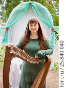 Купить «MOSCOW, RUSSIA - MAY 30, 2015: Young woman harp-player participant of musical Band Polca an Ri stands holding arpa against arch decorated green and white fabrics. Polca an Ri plays trditional irish music.», фото № 25840040, снято 30 мая 2015 г. (c) Losevsky Pavel / Фотобанк Лори