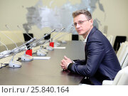 Купить «Young businessman in glasses sitting at negotiating table in conference room», фото № 25840164, снято 10 апреля 2014 г. (c) Losevsky Pavel / Фотобанк Лори
