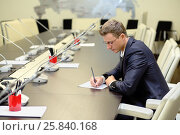 Купить «Young businessman in glasses sitting at negotiating table and writing on paper», фото № 25840168, снято 10 апреля 2014 г. (c) Losevsky Pavel / Фотобанк Лори