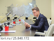 Купить «Young businessman in glasses sitting at negotiating table and reading the document», фото № 25840172, снято 10 апреля 2014 г. (c) Losevsky Pavel / Фотобанк Лори