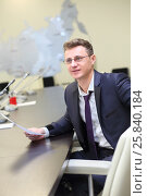 Купить «Happy young businessman in glasses sitting at negotiating table with blank paper in his hands», фото № 25840184, снято 10 апреля 2014 г. (c) Losevsky Pavel / Фотобанк Лори