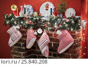 Купить «Fireplace with mantelshelf decorated to christmas holidays by conifer branches, balls, candles, plates, gift boots», фото № 25840208, снято 9 января 2015 г. (c) Losevsky Pavel / Фотобанк Лори