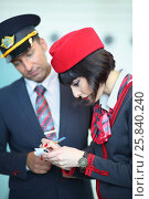 Купить «MOSCOW – JUL 09, 2015: Stewardess in red hat makes an entry in the notebook beside man at DME RUNVAY in Domodedovo», фото № 25840240, снято 9 июля 2015 г. (c) Losevsky Pavel / Фотобанк Лори