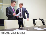 Купить «Two businessmen standing with a blank sheet of paper near conference table», фото № 25840332, снято 10 апреля 2014 г. (c) Losevsky Pavel / Фотобанк Лори