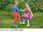 Купить «Boy and girl dressed in red and blue costumes dance at grassy lawn», фото № 25840368, снято 29 мая 2016 г. (c) Losevsky Pavel / Фотобанк Лори