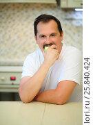 Купить «Happy man with mustache in white bites green apple in kitchen», фото № 25840424, снято 2 сентября 2015 г. (c) Losevsky Pavel / Фотобанк Лори
