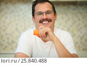 Купить «Happy handsome man in glasses eats orange carrot in kitchen, shallow dof», фото № 25840488, снято 2 сентября 2015 г. (c) Losevsky Pavel / Фотобанк Лори