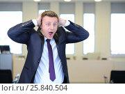 Купить «Very frightened businessman clutched his head in office», фото № 25840504, снято 10 апреля 2014 г. (c) Losevsky Pavel / Фотобанк Лори